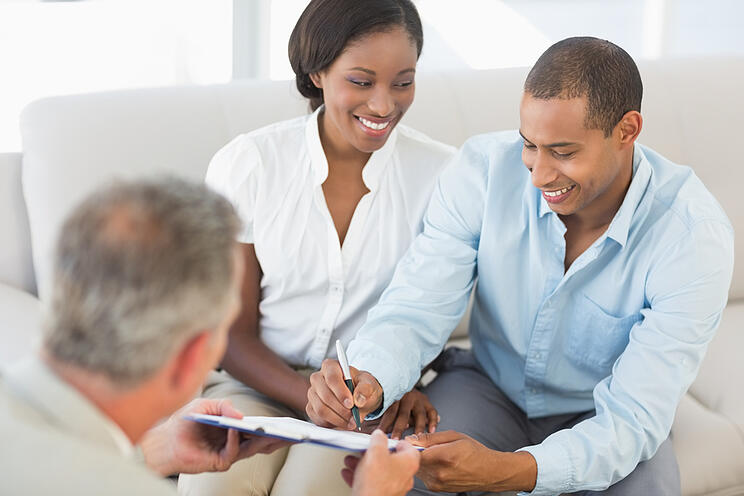 Young smiling couple signing contract on the couch in the office
